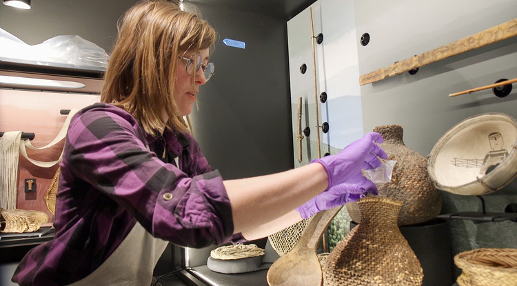 Conservation staff member Betsy Burr prepares the basket exhibit at the Arizona State Museum. (Photo: Bob Demers/UANews)