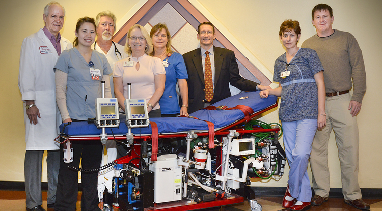 The UAMC ECMO Transport Team includes, from left, Rich Smith, who heads the Mobile Intensive Care Program; ECMO specialists Sonya Sozauski and Mark Quinnan of 4NW; Dr. Robyn Meyer; advanced ECMO specialist Jeanne Scott; ECMO transport surgeon Dr. Jess Thompson; advanced ECMO specialist Misty Duden; and perfusionist Chris Mogan, ECMO coordinator. Not pictured: Kathy Swanson.