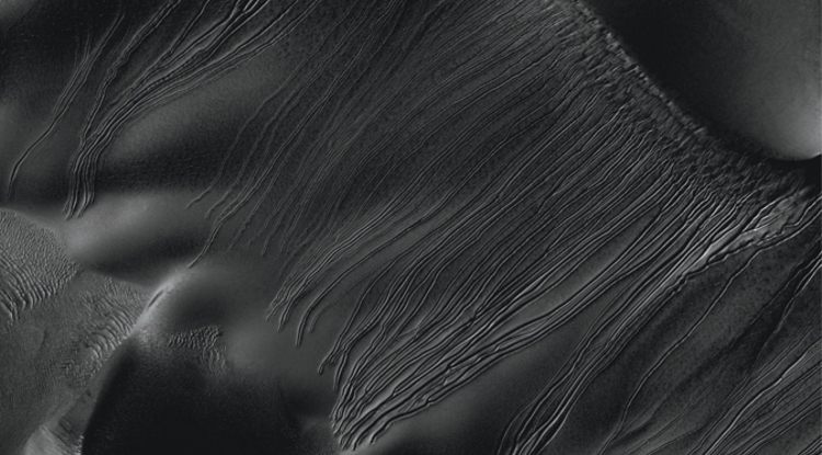 This image from the UA-operated HiRISE camera on NASA's Mars Reconnaissance Orbiter shows linear gullies extending almost 1.2 miles inside Russell Crater. Unlike gullies caused by water-lubricated flows on Earth and possibly on Mars, they don't have aprons of debris at the downhill end of the channel, just an empty pit – most likely left behind by dry-ice chunks. (Photo: NASA/JPL-Caltech/UA)
