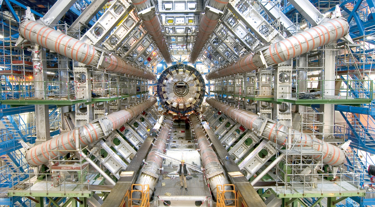 A person stands in front of the huge ATLAS detector, one of six detectors that are part of the Large Hadron Collider near Geneva. The photo was taken before the detector was closed up. (Photo credit: Maximilien Brice, CERN)