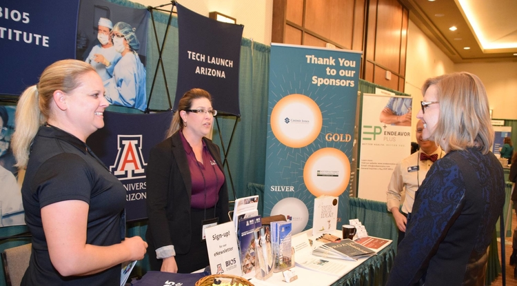 Kelle Hyland and Amy Randall talk with Jennifer Barton at the UA booth at AZBio 2016. The UA's contributions to the bioscience industry have been increasingly significant. (Photo: Mark Goldstein)