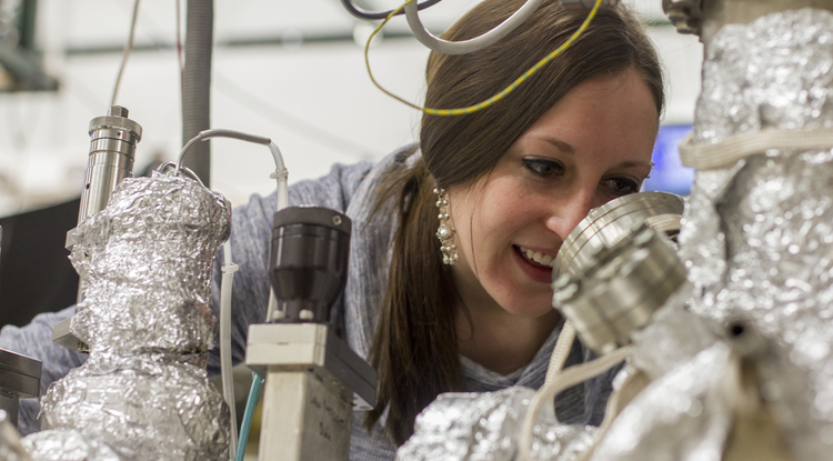 Calley Eads inspects a sample in the vacuum chamber to get it ready for measurement. (Photo: Kyle Mittan/UANews)