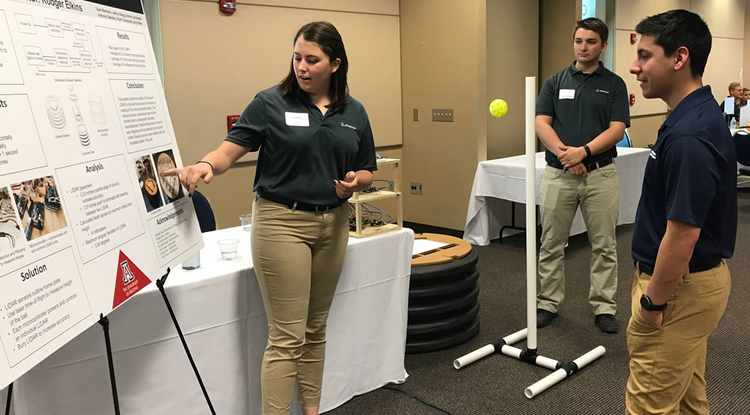 Engineering students demonstrate how RoboUmp, their robotic umpire, works. The project utilizes the accuracy of lidar, a pulsed laser used to measure distances, and LED technology. (Photo: David Hostetler)