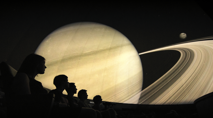 Surrounded by spectacular sights and sound, audience members enjoy a journey to Saturn and its rings. The new Flandrau FullDome system even makes it possible for visitors to take the controls and fly right into the rocky debris that make up the rings. (Image courtesy of Flandrau Science Center)