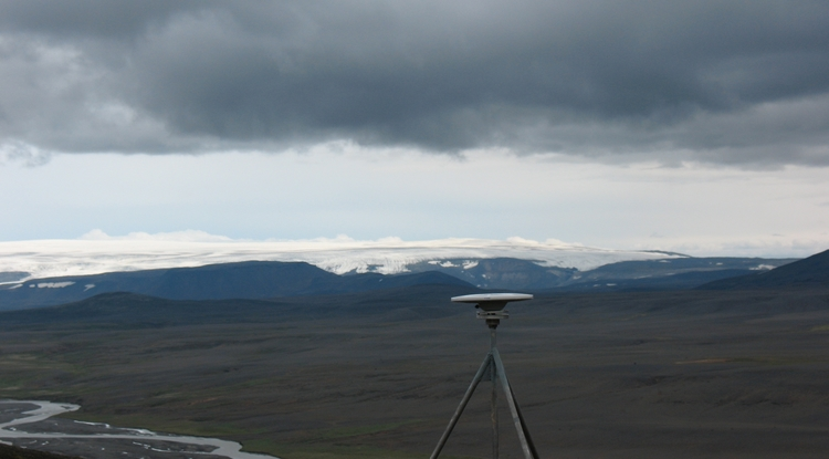 This global positioning satellite receiver is part of Iceland's network of 62 such receivers that geoscientists are using to detect movements of the Icelandic crust that are as small as one millimeter per year. Langjokull glacier is in the background. (Photo: Richard A. Bennett/UA Department of Geosciences)