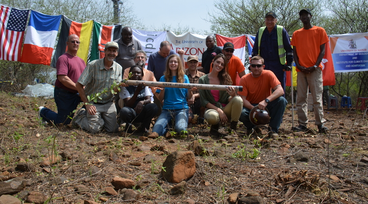 The Hominin Sites and Paleolakes Drilling Project scientific drilling team holds the final core segment collected at the Tugen Hills drill site, from approximately 750 feet below the earth's surface. Flags represent countries and institutions involved in the project. (Front row: team members Alan Deino, Andrew Cohen, Gladys Tuitoek, Sarah Ivory, Jessamy Doman, Beau Marshall. Back row: Steven Rucina, Anders Noren, Chad Yost, David Mbuthia, Mike Scarpellini, Dennis Njagi. (Photo courtesy of the Hominin Sites and Paleolakes Drilling Project)