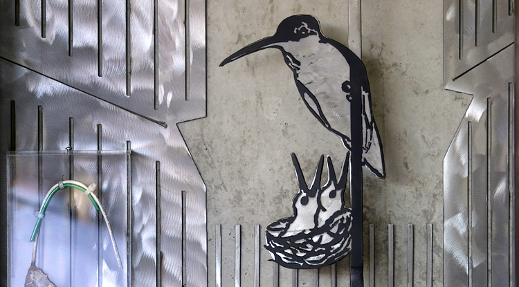 "The first ""residents"" of the UA's ENR2 building — a mother hummingbird and her two babies — are now memorialized on the building's fifth floor. In the installment's lower left corner is part of the original nest and the data cable to which it was attached. (Photo: Bob Demers/UANews)"
