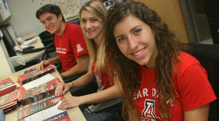Student assistants (left to right) Ivan Almirudis, an aerospace engineering sophomore; Janae Van Buren, a public health junior; and Katelyn Raynak, a senior majoring in Spanish, began preparing welcome packets  on Oct. 11 for mailing to students across the nation.