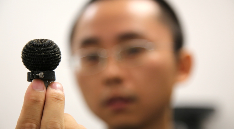 Co-inventor Min Liang holds the new 3-D-printed Luneberg lens. (Photo: Paul Tumarkin/Tech Launch Arizona)