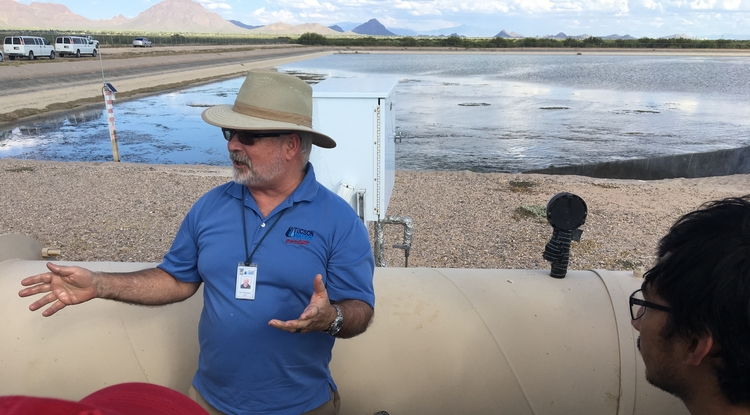 Tucson Water hydrologist Dick Thompson, a UA alumnus (2005), talks to a UA hydrology class about groundwater recharge. Tucson Water uses the pond in the background to recharge the groundwater with Central Arizona Project water. (Photo: Martha Whitaker/UA Department of Hydrology and Atmospheric Sciences)