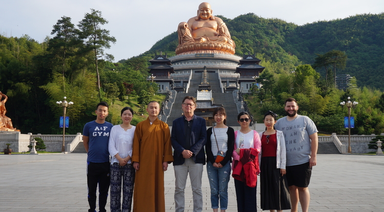 In front of the statue of Maitreya Buddha at Xuedou (Snow Pass) Monastery with the abbot, UA professor Albert Welter and UA graduate students