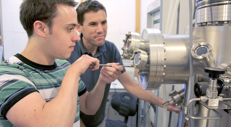 Brian LeRoy, UA associate professor of physics (right) and graduate student and first author of the study, Matthew Yankowitz, use a tunneling electron microscope to probe the electronic properties of graphene. (Photo: Daniel Stolte/UANews)
