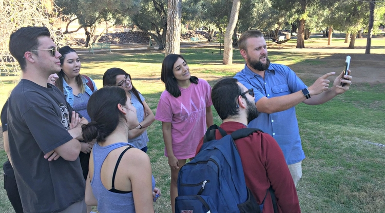 Michael McKisson shows students how to use the school's new 360-degree cameras, which can be attached to iPhones. (Photo: Mike Chesnick/UA School of Journalism)