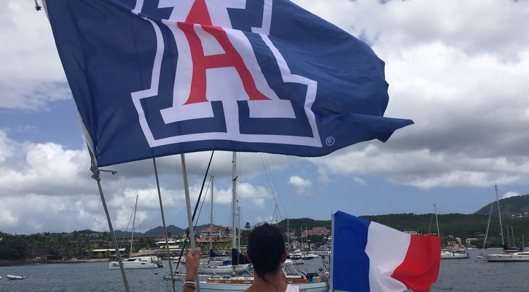 Student Rachel Franke flies the UA flag in Martinique during the Arizona in the French Caribbean Program, run through the College of Humanities with support from UA Study Abroad in the Office of Global Initiatives.