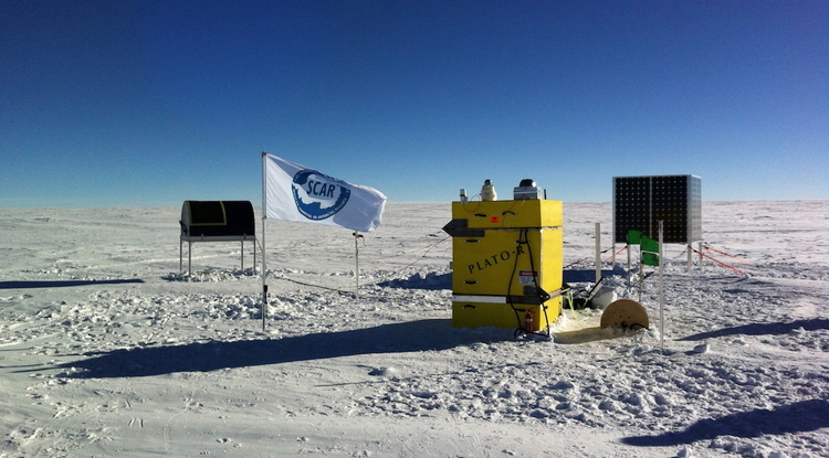 An oddity on a barren snowy plateau, an astronomical observatory watches the skies. From left, the mailbox-like HEAT telescope, the yellow PLATO-R instrument module with cameras and antennas on the rooftop and a cube of solar panels to power the observatory in the summer. (Photo: Craig Kulesa)