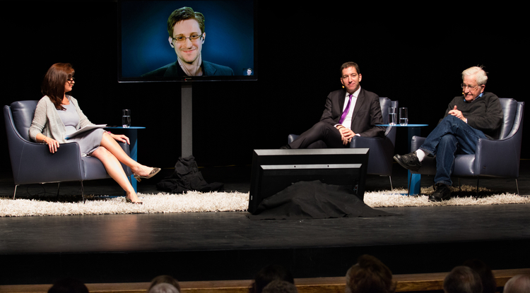 """A Conversation on Privacy"" at the UA's Centennial Hall featured (from left) moderator Nuala O'Connor, Edward Snowden (on video screen), Glenn Greenwald and Noam Chomsky. (Photo: Ernesto Trejo/UANews)"