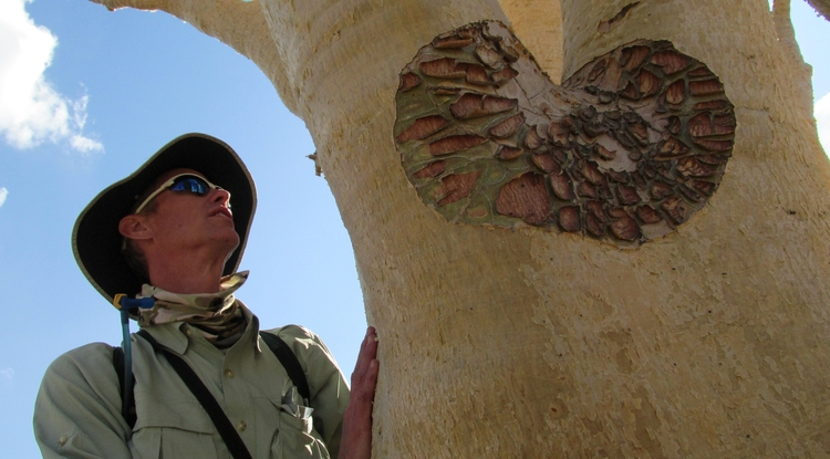 Tom Wilson points out the water storing adaptations of this caudiciform (fat-stemmed plant) just outside the capital Windhoek in central Namibia. Its skin peels to protect it from high transpiration rates, extreme fluctuations in temperature and sunburn. (Photo by Michaela Brumbaugh)