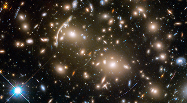 The Hubble Space Telescope took this image of Abell 370, a galaxy cluster 4 billion light-years from Earth. Several hundred galaxies are tied together by gravity. The arcs of blue light are distorted images of galaxies far behind the cluster, too faint for Hubble to see directly. (Image: NASA, ESA, and J. Lotz and the HFF Team/STScI)