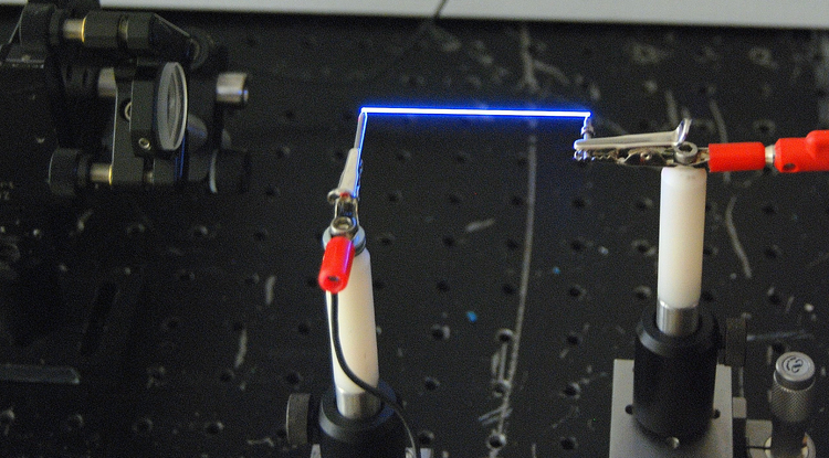 Miniature lightning: The team used a femtosecond laser to create a thin column of plasma – a special charged state of matter – in the air between two electrodes. (Photo by Pavel Polynkin)