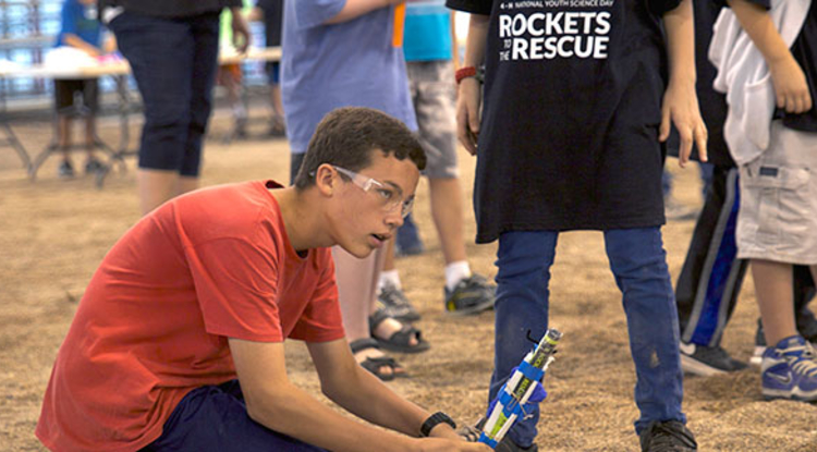 A 4-H National Youth Science Day participant prepares a rocket for launch. (Photo: Ian Brewer)