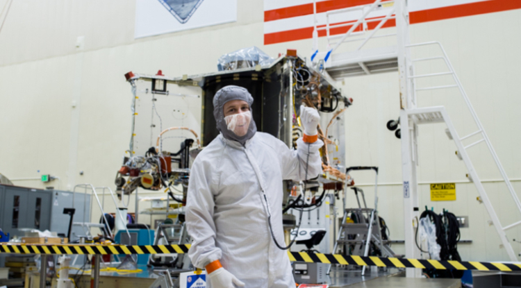 Systems engineer Bradley Williams with the OSIRIS-REx spacecraft in the Lockheed Martin cleanroom.
