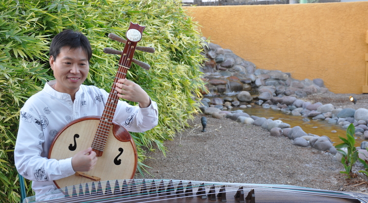 Dongxiao Zhang, music director of the Zhongshan University Chinese Orchestra, will introduce students to two traditional Chinese instruments - the ruan (which he holds in his hands above) and the guzheng.