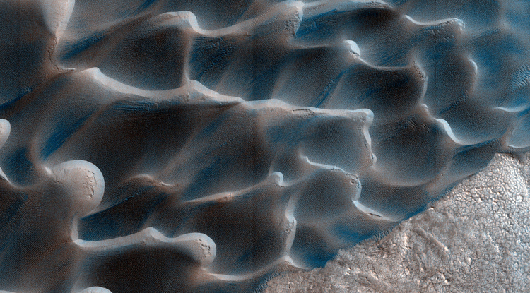 The retreat of Mars' polar cap of frozen carbon dioxide during the spring and summer generates winds that drive the largest movements of sand dunes observed on the red planet. (Image: NASA/JPL/University of Arizona/USGS)