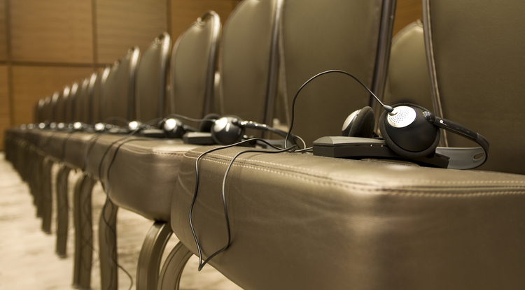 Tools of the trade: translation headphones await participants in a business conference room.