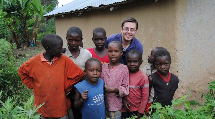 Students in the UA's BRAVO! program work abroad in labs run by colleagues of UA faculty. Here, Jonathan Schouest, who is pursuing a master's degree in public health, poses with a group of Kenyan children.