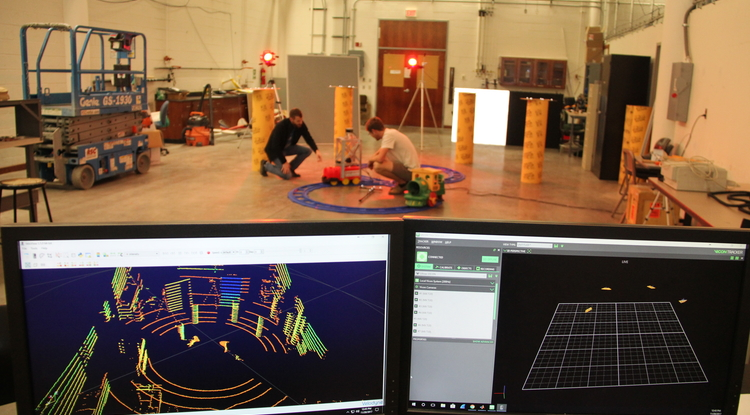 NavLab manager Nick Morris (left) and undergraduate researcher Nicholas Patzke set up a test vehicle that is tracked by a Vicon camera and a lidar system, seen on the monitors in the foreground. (Photo: Pete Brown/UA College of Engineering)