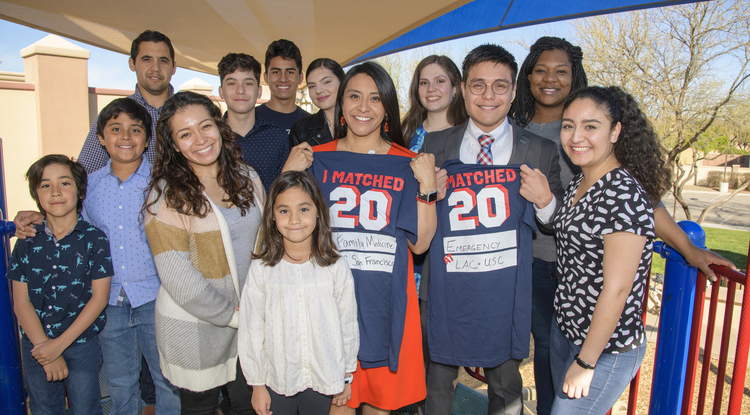 Match Day typically draws hundreds of student and families. This year, amid COVID-19 concerns, the traditional ceremony was canceled, and students celebrated virtually or with small groups of family and friends instead. College of Medicine Tucson students Cazandra Zaragoza and Ivan Aispuro (holding T-shirts) celebrated with loved ones at a local park. (Photo: Kris Hanning/University of Arizona Health Sciences)