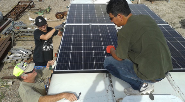 Members of the UA-AATech team mount the solar panels on the roof of the school bus. From left: Bob Seaman, technical lead for desalination unit assembly; environmental engineering master's student Chris Yazzie; and AATech president Peter Zhou. Yazzie was raised on the reservation and is writing his master's thesis on the separation of uranium from water.