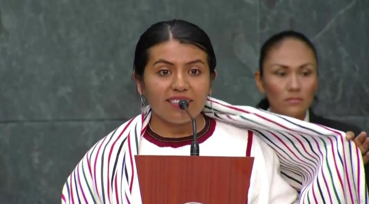 Tania Martínez Cruz explains the significance of her striped scarf to the audience as she accepts her prize at the Mexico City residence of President Enrique Peña Nieto. (Photo courtesy of nvinoticias.com)