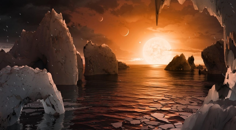 "An artist's impression of the perpetual sunrise that might greet visitors on the surface of planet TRAPPIST-1f. If the planet is tidally locked, the ""terminator region"" dividing the night side and day side of the planet could be a place where life might take hold, even if the day side is bombarded by energetic protons. In this image, TRAPPIST-1e can be seen as a crescent in the upper left of the image, d is the middle crescent, and c is a bright dot next to the star. Image credit: NASA/JPL-Caltech"