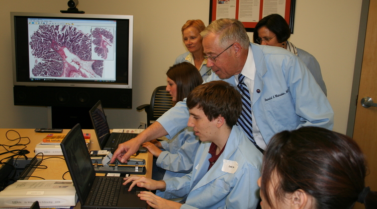 "Dr. Ronald S. Weinstein and Dr. Anna R. Graham teach pathology to Sir William Osler High School Fellowship summer students. The high school students are viewing a ""virtual slide"" of a human bowel tumor."