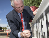 UA President Robert C. Robbins signs the final steel beam. (Kris Hanning/UAHS BioCommunications)