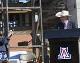 Neumayer takes a photo of Robbins wearing a cowboy hat he borrowed to shield his eyes from the sun. (Kris Hanning/UAHS BioCommunications)