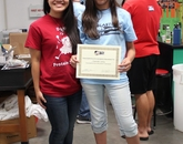 A student, Savannah (right), receives her certificate of BlastOff! camp completion from Biochemistry Club president Gloria Le.