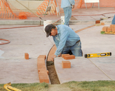 UA mason Eugene Kiley works on a section of the track that creates a full-scale outline of the USS Arizona.