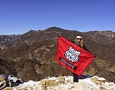 Alumna Taylor Baumgarten, who earned a degree in public health, holds a UA flag at the Great Wall of China.