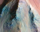 Giant Valles Marineris is up to 10 kilometers deep; this is just a small part near the bottom of a giant slope connecting the upper plains to the canyon floor. The varied colors indicate a mix of altered and unaltered rocks in this deep exposure of ancient Mars.