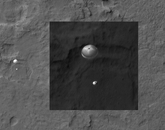 The Descent of Curiosity: NASA's Mars Science Laboratory, Curiosity, was spotted by HiRISE as it descended to the surface on Aug. 5, 2012. Curiosity and its parachute are on the left, while above is a close-up, stretched to avoid saturation. The rover is landing on the etched plains just north of the sand dunes that fringe Aeolis Mons (informally called Mount Sharp) within Gale Crater.