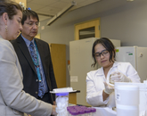 Paloma Beamer's doctoral student, Yoshira Ornealas Van Horne (right), inspects a water sample brought by Navajo Nation Vice President Jonathon Nez.