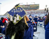 Maya Wallace, an agricultural technology, management and education graduate from Tucson, plans to attend graduate school in the fall. Her mortarboard is decorated with the finishing command she uses with her trained border collies at home. (Photo: John de Dios/UANews)