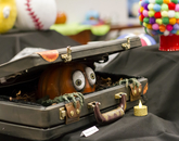 A decorated pumpkin, with hands and arms, appears to be eerily crawling out of a suitcase.
