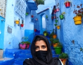 """Simran Heer's photo """"City of Skies"""" earned the grand prize for 2017. Heer poses in black garb amid the backdrop of blue walls in the Moroccan city of Chefchaouen during a getaway from her CEA in France study-abroad trip."""