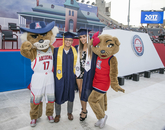 Graduates take a moment to pose with Wilbur and Wilma Wildcat.