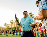 Miguel Flores walks the circle of participants, extending a blessing to each of them.