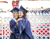 Rachelle Pilapil, a graduate in criminal justice, and Rachel Zaner, a dance major, embrace at Commencement. (Photo: John de Dios/UANews)