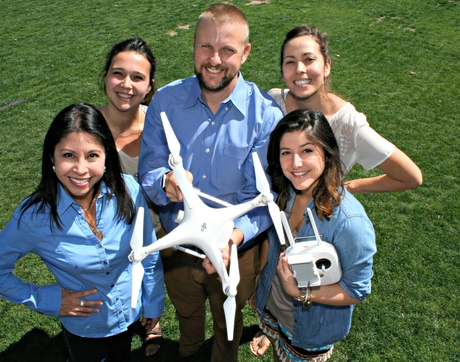 UA journalism multimedia professor Michael McKisson shows off the school's new drone with (from left) professor Celeste González de Bustamante, journalism senior Christianna Silva, and graduate students Kendal Blust and Jennifer Hijazi. (Photo by Mike Chesnick)